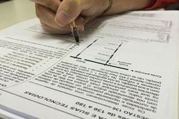 Imagem em close da mão de uma pessoa resolvendo questões do caderno de prova do Enem