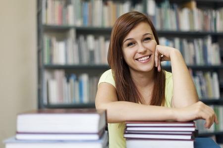 Foto retangular de uma jovem estudante em uma biblioteca. Ela é branca, tem cabelos longos, lisos e castanhos, veste blusa branca e está sentada de frente para a câmera diante de uma mesa cheia de livros.